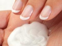 Beautiful female hand applying moisturiser close up